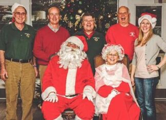 Lions (from left) Bill Muensch, Joe Marquedant, Don Cronin, Bob Chesmore and Christine Curren stand behind the Sullivans as Santa and Mrs. Claus.