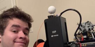 Hopkinton High School senior Tyler Rhodes poses with his 3D printer
