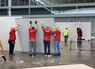 Workers put up cubicles at Boston Convention and Exposition Center