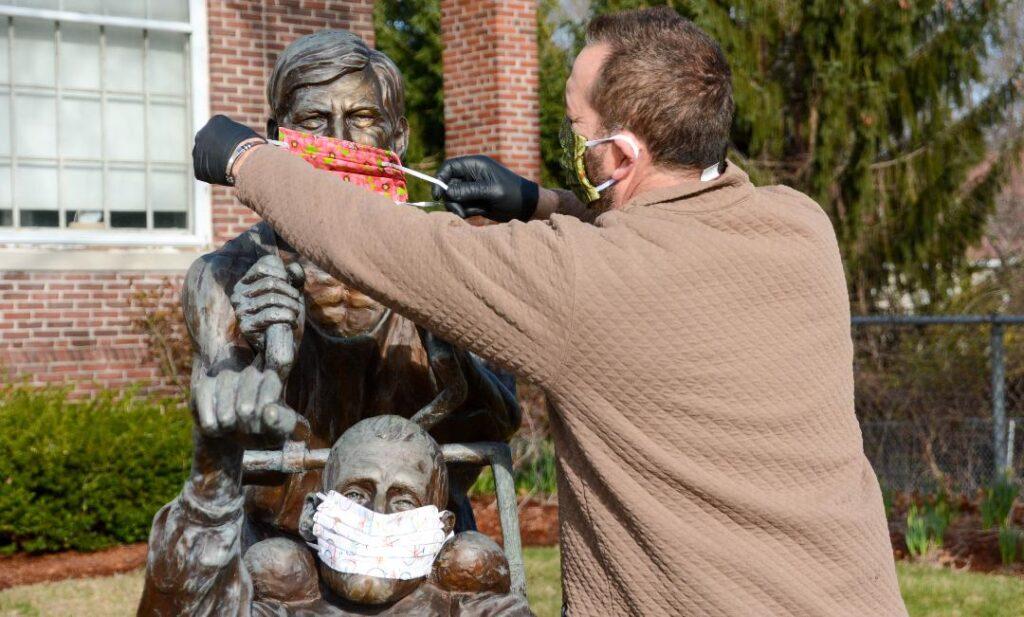 John Coutinho putting protective masks on Team Hoyt statue